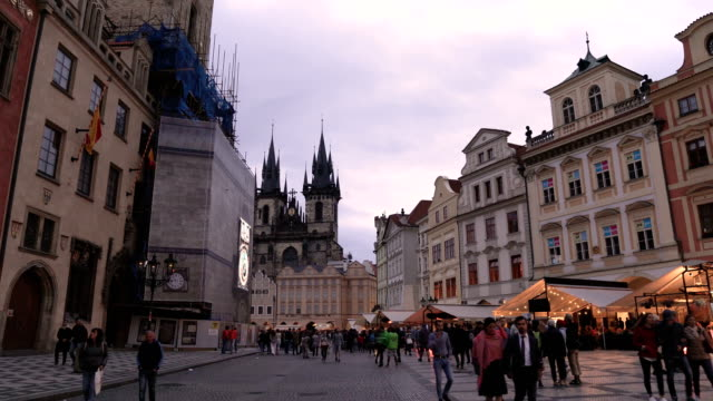 handheld walking view into old square containing crowd of traveller in Prague at evening, Czech Republic