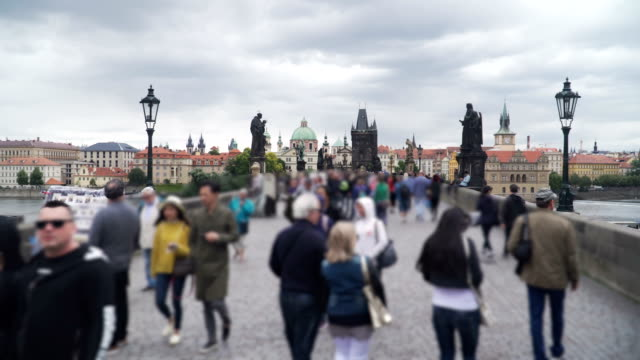 vídeos de stock e filmes b-roll de handheld walking view of charles bridge in prague during raining day, czech republic. - república checa