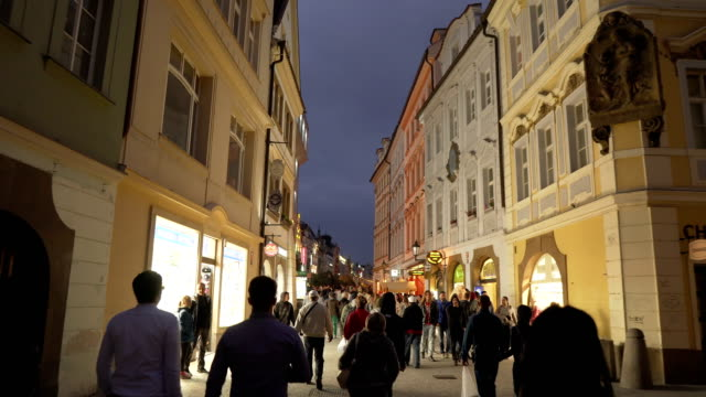 handheld walking view on local market street in old square containing crowd of traveller in prague at evening, czech republic - prague old town square stock videos & royalty-free footage
