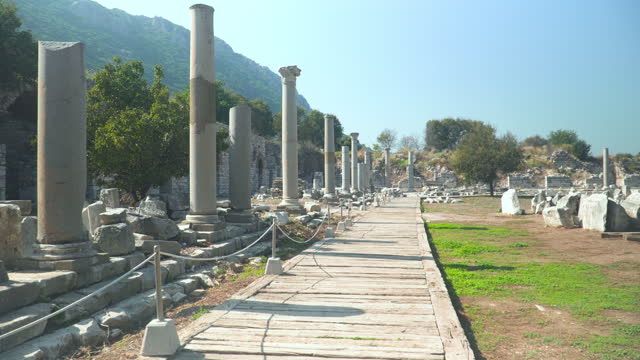 vídeos de stock e filmes b-roll de handheld walking view while traveling in old ruin architectural corridor and pillar at one part of the library of celsus, ephesus, kusadasi turkey. travel destination of marble arch and sculpture in a classical greek era, anatolia under a blue sky. - arqueologia