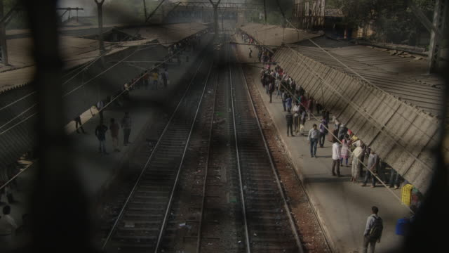 Handheld wide shot of people waiting on station platforms as seen through the mesh of a railway bridge, Mumbai, Maharashtra, India.