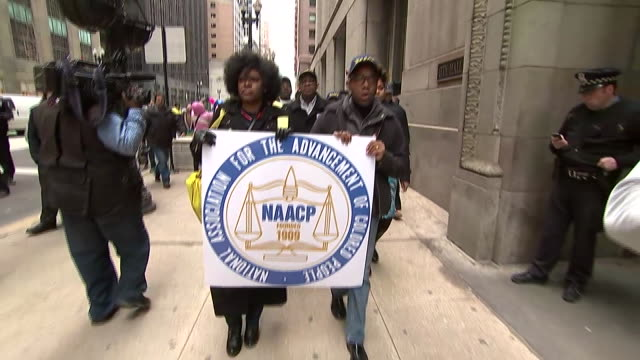 handheld wide tracking shot of protesters marching at the front of racial demonstration in chicago. they hold a sign for the naacp and sign a gospel,... - naacp stock videos & royalty-free footage