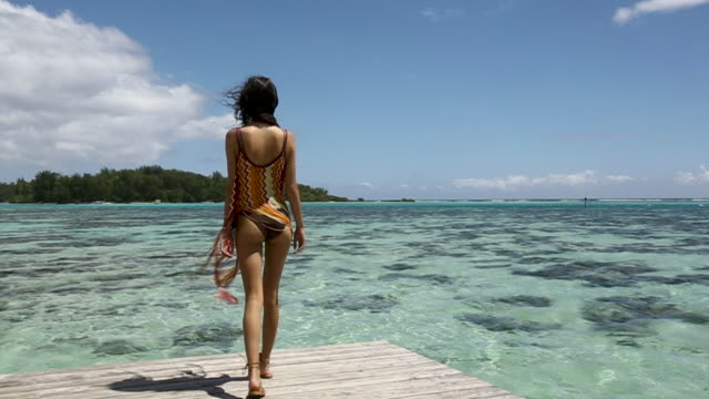 handheld, woman walks on dock in tahiti - tahiti stock videos & royalty-free footage