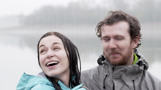 cu handheld young couple chatting and laughing  in pouring rain - rain stock videos & royalty-free footage