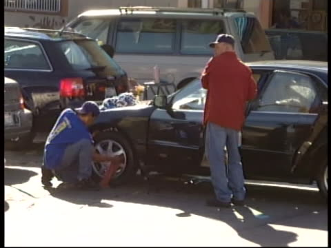 hand-held zoom out of two immigrant worker cleaning the tires and windows of a sports car at a car wash. immigrant, òmigrant,ó or òforeignó workers... - car wash stock videos & royalty-free footage