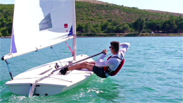 hd handheld:shot of young boats-man sailing on laser class boat - small boat stock videos & royalty-free footage