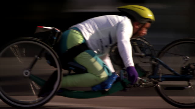 A handicapped marathoner leans forward as he races his wheelchair on a city street.