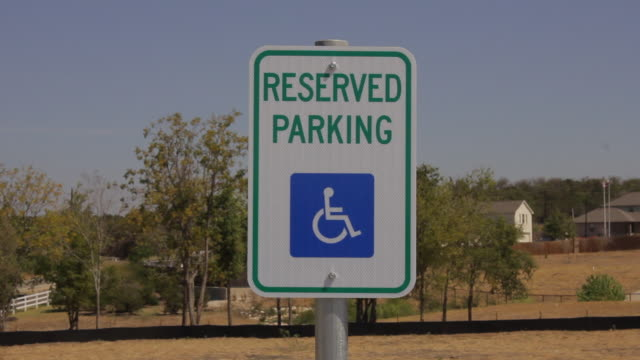 handicapped reserved parking sign farmland in background - tecnologia assistiva video stock e b–roll