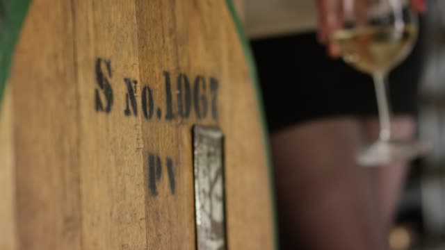 handing holding a wine glass next to a wood barrel