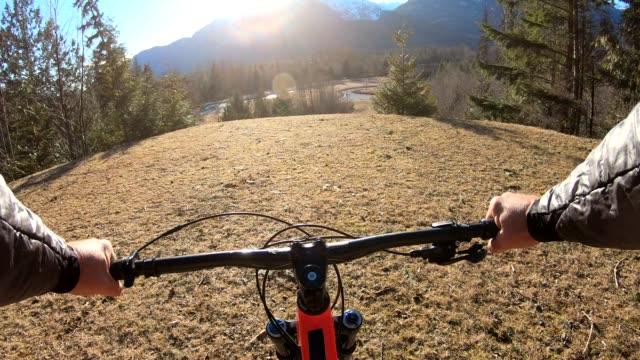 POV handlebar view, mountain biker traverses meadow