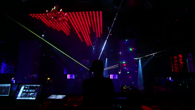 vidéos et rushes de dj handling the sound mixer in a nightclub - dj