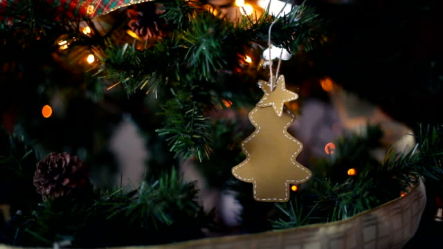 Handmade cardboard pine ornament with a star on the top hanging from Christmas tree.