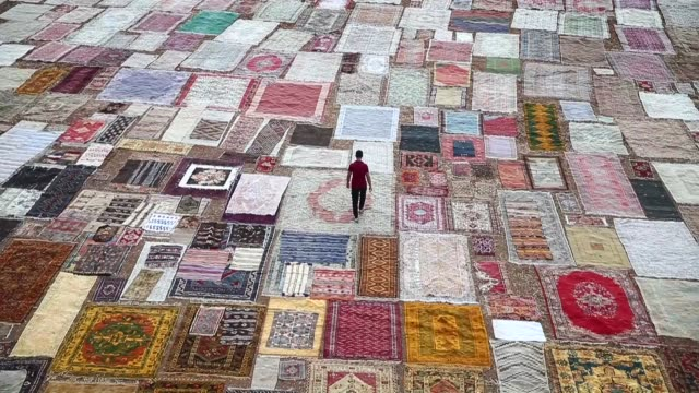 hand-made carpets, brought from varied regions of turkey, are laid under the sun on a field to soften their color in dosemealti district of turkey's... - made in usa点の映像素材/bロール