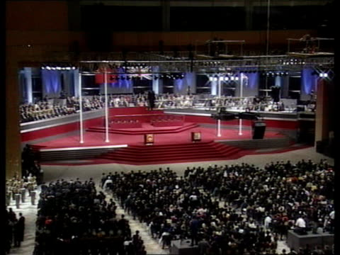 handover events convention centre gv crowds in hall for handover ceremony as military band play sot general sir charles guthrie leads british... - 式典点の映像素材/bロール