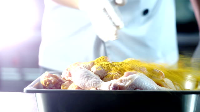 Hands adding curry powder to raw chicken legs for cooking.