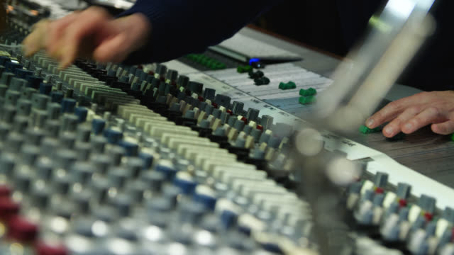 vídeos de stock e filmes b-roll de hands adjust dials and channel faders on an analogue sound mixing desk - disco audio analógico