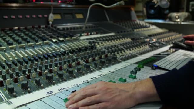 vidéos et rushes de hands adjust levels and tap a computer keyboard on a sound mixing desk - mélanger