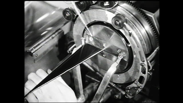 vídeos de stock e filmes b-roll de hands adjusting strings while turning the wheels of a machine; close up of hands adjusting mechanism of machine; invoice; machinery being adjusted... - 1940 1949