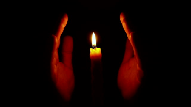 Hands approaching burning candle