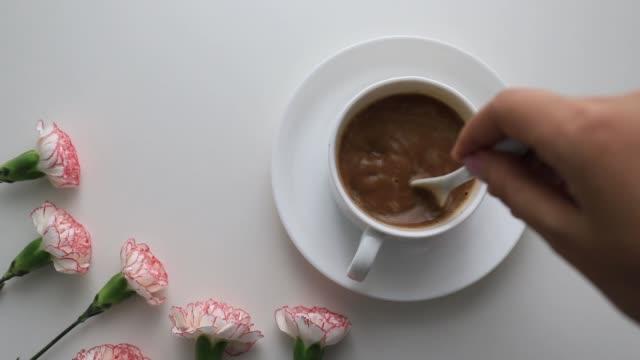 vídeos y material grabado en eventos de stock de las manos se elaboran en una taza de café colocada sobre una mesa blanca. con flores decoradas - ranúnculo