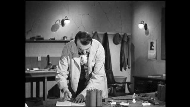 hands attaching wires to row of large batteries on the table; scientist listening to the ear piece and flips through a book - 1940 1949 bildbanksvideor och videomaterial från bakom kulisserna