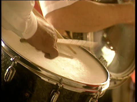 vidéos et rushes de hands beat drumsticks onto drum tilt up to hand strumming banjo - drummer