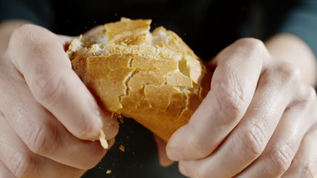 slo mo hands breaking a baguette in half - white bread stock videos and b-roll footage