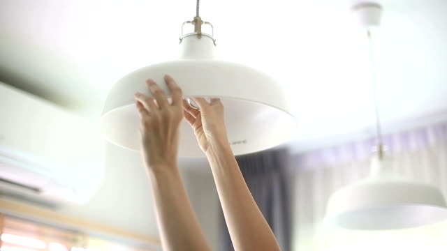 Hands changing retro bulb to LED.