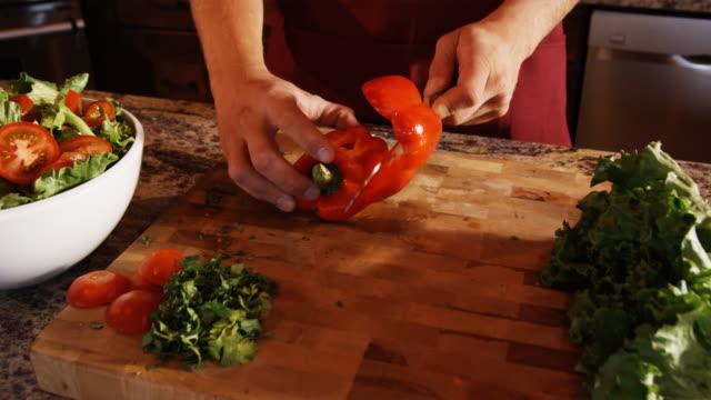hands chopping a red pepper