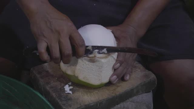 Hände, die Kokosnuss mit einem Messer hacken