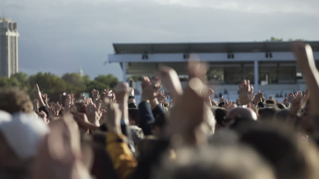 vidéos et rushes de hands clapping at an out door concert - fist