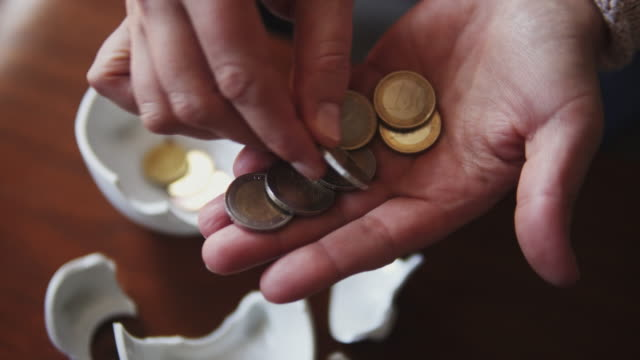 hands counting coins from broken piggy bank. - savings stock videos & royalty-free footage