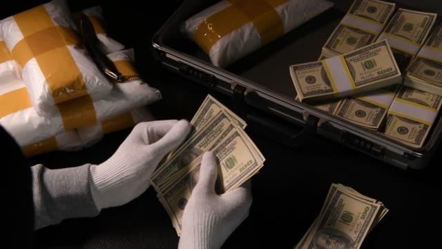 vídeos de stock, filmes e b-roll de mãos contando dinheiro com pacotes de drogas narcóticas e dinheiro no fundo - smuggling