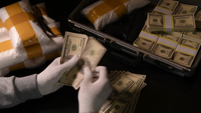Hands counting money with packs of narcotic drugs and money in the background