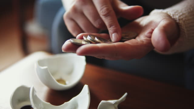 hands counting savings coins from piggy bank. - currency symbol stock videos & royalty-free footage