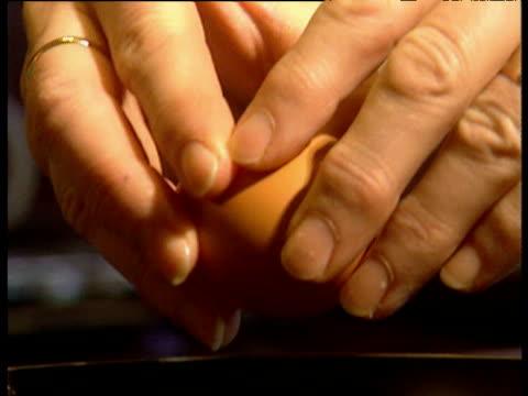 vídeos de stock e filmes b-roll de hands crack open egg into frying pan to produce perfect fried egg uk - 1990