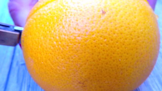 Hands cutting fresh orange on kitchen