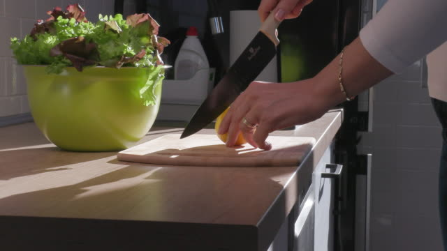 hands cutting lemon in half on cutting board to season salad - salad bowl stock videos & royalty-free footage
