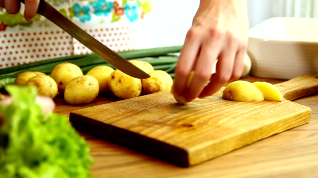 Hands cutting potatoes on wooden board.