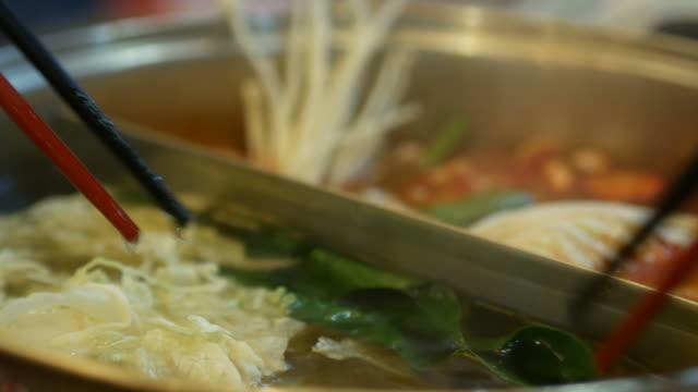 vídeos de stock, filmes e b-roll de mão comer com pauzinhos, sukiyaki, shabu-shabu - comida japonesa