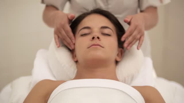 tu hands giving woman a facial treatment / stowe, vermont, united states - 美容専門家点の映像素材/bロール