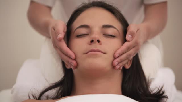 tu hands giving woman a facial treatment / stowe, vermont, united states - schönheitssalon stock-videos und b-roll-filmmaterial