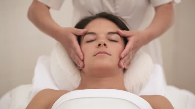 tu hands giving woman facial treatment / stowe, vermont, united states - facial massage stock videos and b-roll footage