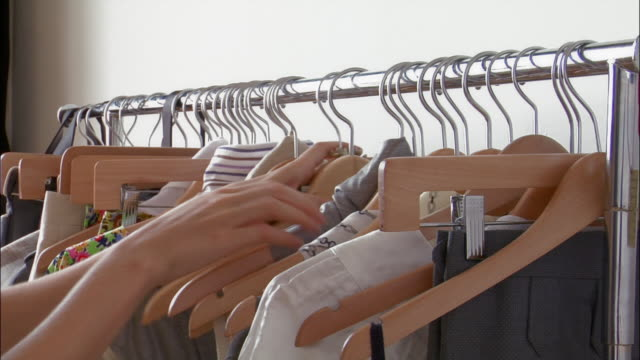 vídeos y material grabado en eventos de stock de hands going through clothes hanging on rack / removing article of clothing - barra para colgar la ropa