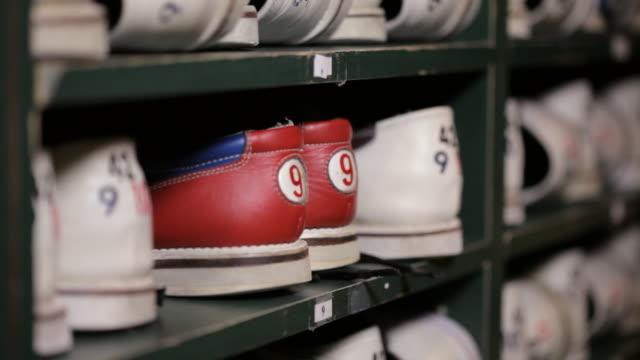 vídeos de stock, filmes e b-roll de hands grab pair of bowling shoes from a shelf - sapato de boliche