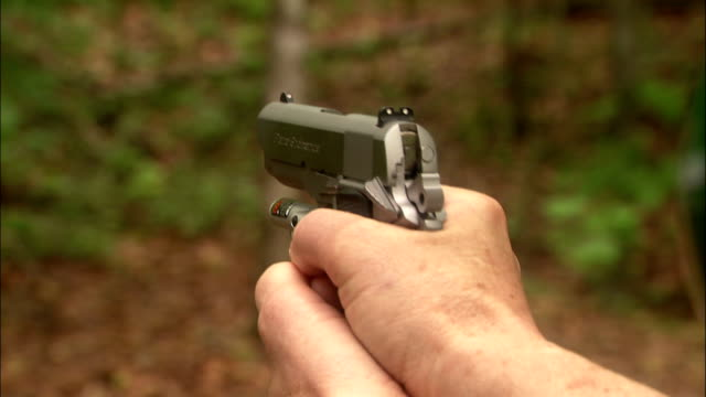 hands grip a pistol and fire. - handgun stock videos & royalty-free footage