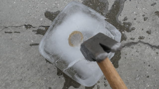 hands hammering a block of ice with the money inside, hammer breaks the ice to take the 1 euro coin trapped inside an ice cube, economic crisis, frozen economy concept video stock - frozen stock videos & royalty-free footage