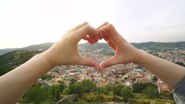 Hands heart shaped above the cityscape.