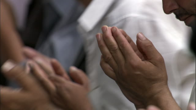 Hands held in a position of prayer in mosque, Kashgar, Xinjiang province, China