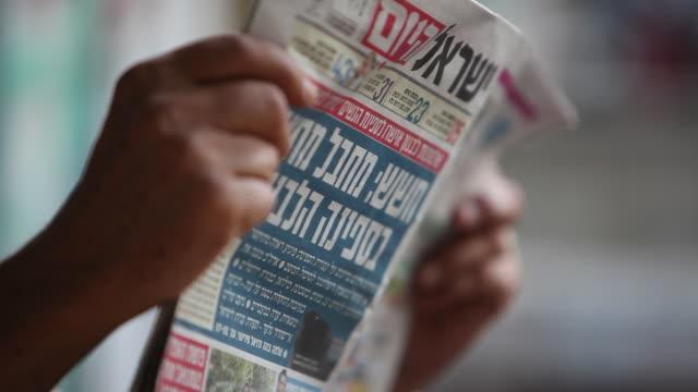 Hands hold an Israeli newspaper.